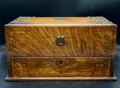 An oak tea caddy with sliding drawers and white metal detail.