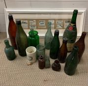 A selection of vintage beer bottles and others along with a framed vintage advertising clippings and