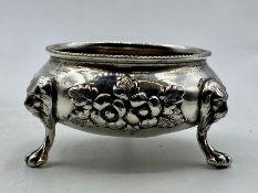 A silver cruet on claw feet.