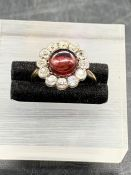 A Ruby and Diamond daisy style ring on a yellow gold setting. central ruby surrounded by twelve