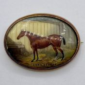 An enamel brooch of a racehorse 'Lord George' set in 18 ct gold with safety chain (Total weight 17.