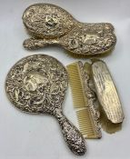 A selection of silver backed dressing table brushes and a mirror