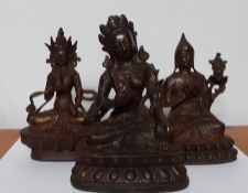A group of three figures in bronze and cast iron representing Tara and Guanyin. (17 cm largest).