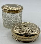 A silver lidded glass jar and a silver lid.