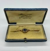 A Bar Gold Brooch with oval blue sapphire 6.5mm x 4.5mm, surrounded by 8 half seed pearls. Stamped
