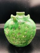 An Antique Chinese green bottle with writing to both sides.
