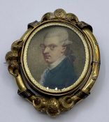 "A rotating Pinchbeck brooch with miniature portraits of a Gentleman and a Lady ""Containing a"