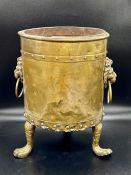 A brass plant pot on claw feet and lion head handles