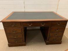 A large oak pedestal desk with leather top (H76cm W150cm D91cm)