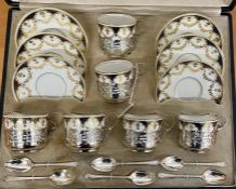 A cased set of six Aynsley porcelain teacups, saucers mounted in pierced silver stands. Presentation