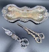 A candle snuffer and a pair of grape scissors and a tray.
