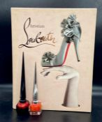 A large Christian Louboutin reference book by Rizzoli New York with two collectable Louboutin Beauty