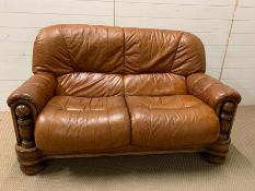 A leather two seater sofa (H95cm W140cm D80cm)
