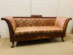 A classical style settee with out scrolled arms upholstered seat over a carved frame ending in