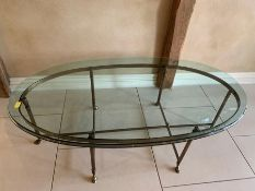 An oval glass coffee table on metal legs terminating on camel style feet L130 x H42 X W72cm