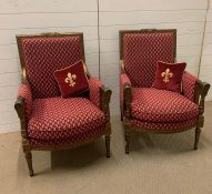 A pair of gilt armchairs in a Louis XVI style on turned tapering fluted legs