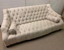 A three seater cream button back sofa