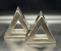 A pair of triangular white metal book ends