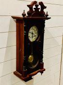 A mahogany wall hanging clock