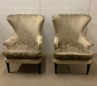 A pair of contemporary wing back chairs with sleek design to arms on ebony style legs