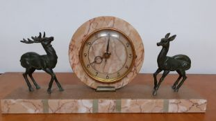 An Art Deco mantel clock, mounted with two deer's, the dial with Arabic numerals, (restauration), (