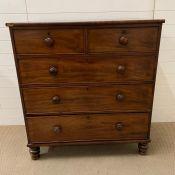 A mahogany chest of drawers on turned bun feet (H116cm W107cm D55cm)