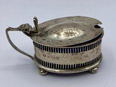 A Birmingham hallmarked silver mustard salt with blue glass.