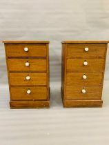 A pair of tall pine bedsides with white knobs to the four drawers (H75cm W46cm D43cm)