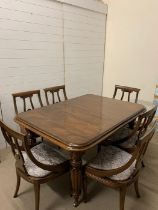 A six seater dining table with two extension leaves on reeded legs (H76cm W150cm D109cm extensions