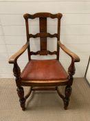 An oak open armchair with oxblood seat cushion