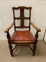 An oak open armchair with oxblood seat cushion