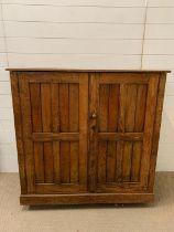 An oak two door cupboard with one internal shelf (H107cm W112cm D47cm)