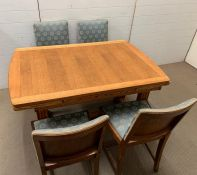An oak table with reeded legs, extends both sides and four matching chairs (H77cm W126cm D84cm)