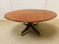 A low oval centre/coffee table with brass claw feet (H46cm W120cm D80cm)