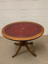 An oval side table with leather top on splayed feet (H53cm W47cm)