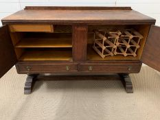An oak sideboard with brass fittings and doors opening to reveal cutlery drawer and shelves