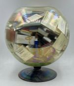 A large collection of matchboxes in a fishbowl shaped vase