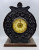An enamel faced circular carved mantel clock.