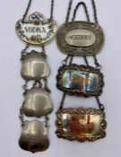 Seven decanter labels in white metal and one china Coalport one.