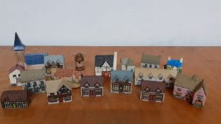 A collection of seventeen collectable miniature ceramic and pottery hand painted houses, made in