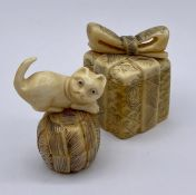 Two carved lidded netsukes, one a box with a bow and the other a cat on a ball of wool.