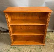 A pine open bookcase on bun feet (H105cm W95cm D30cm)