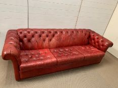 A large three seater vintage red leather Chesterfield sofa (H65cm W220cm D82cm seat H41cm)