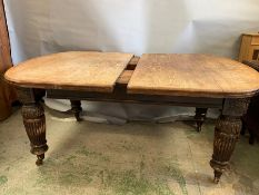 A Victorian mahogany extending dining table with turned and reeded legs ending in castors, one extra