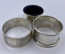 Two hallmarked silver napkin rings and a silver salt with a blue glass liner.