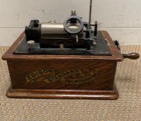 An Edison Standard phonograph, black japanned metal in oak case.