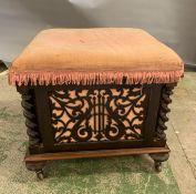 A mahogany music stool with pierced panels and barley twist pillars to corners on turned feet