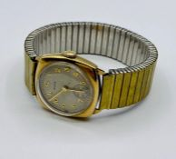 A 9ct gold Hirco watch on stainless steel strap.