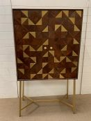 An Adamstown bar cabinet with geometric finish to front on brushed brass handles and legs by Mercury