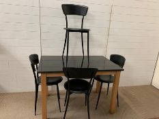 A granite top kitchen table with four Mid Century Italian black chairs (H74cm W110cm D70cm)